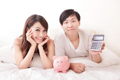 Счастливые пары с розовыми копилкой и калькулятором Стоковое Изображение