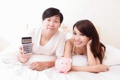 Счастливые пары с розовыми копилкой и калькулятором Стоковая Фотография
