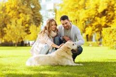 Счастливые пары с собакой labrador в городе осени паркуют Стоковые Изображения RF