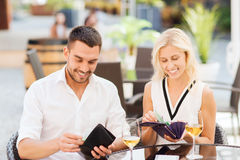 Счастливые пары с счетом бумажника оплачивая на ресторане Стоковые Фотографии RF