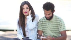 Счастливые пары слушая к музыке совместно, делящ наушники сток-видео