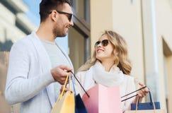 Счастливые пары с хозяйственными сумками на улице города Стоковое Изображение RF