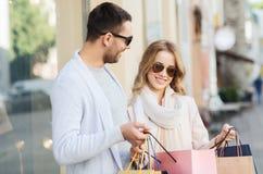 Счастливые пары с хозяйственными сумками на улице города Стоковые Изображения