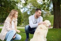 Счастливые пары с labrador выслеживают идти в город Стоковое Изображение