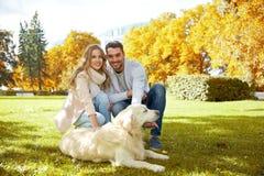 Счастливые пары с labrador выслеживают идти в город Стоковые Изображения