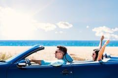 Счастливые пары управляя автомобилем с откидным верхом Стоковые Изображения RF