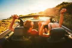 Счастливые пары управляя в автомобиле с откидным верхом Стоковое фото RF