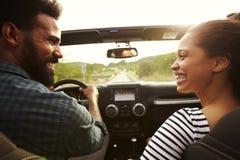 Счастливые пары управляя в их автомобиле смотря один другого Стоковое Изображение