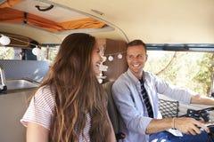 Счастливые пары управляя жилым фургоном смотря один другого Стоковые Изображения RF