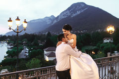 Счастливые пары экономно расходуют и жена обнимая на балконе в выравниваться близко Стоковое Изображение