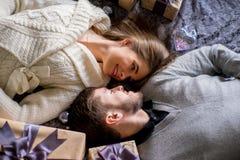 Счастливые пары любовников лежа между подарками рождества Стоковые Фотографии RF