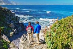 Счастливые пары hiking и смотря красивый вид на океан стоковое изображение