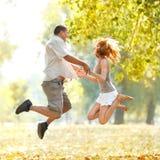 Счастливые пары jamping в парке Стоковые Изображения