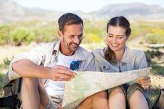 Счастливые пешие пары читая карту на горной тропе стоковая фотография