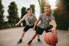 Счастливые подростки играя баскетбол Стоковое Изображение