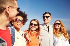 Счастливые подростковые друзья в тенях говоря на улице Стоковое Изображение RF
