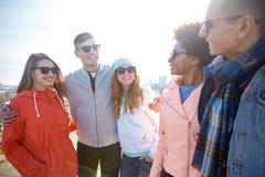 Счастливые подростковые друзья в тенях говоря на улице Стоковое Изображение