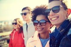 Счастливые подростковые друзья в тенях обнимая на улице Стоковое фото RF
