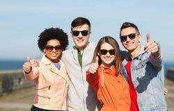 Счастливые подростковые друзья в тенях обнимая outdoors Стоковое Фото