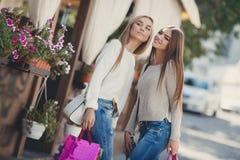 Счастливые подруги идут ходить по магазинам на моле Стоковая Фотография