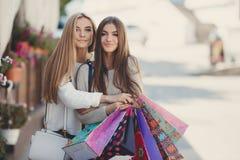Счастливые подруги идут ходить по магазинам на моле Стоковое Фото