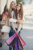 Счастливые подруги идут ходить по магазинам на моле Стоковая Фотография RF