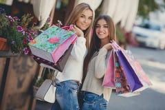 Счастливые подруги идут ходить по магазинам на моле Стоковые Фотографии RF