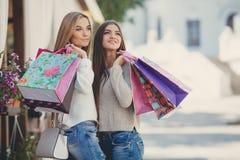 Счастливые подруги идут ходить по магазинам на моле Стоковые Фото
