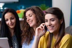 Счастливые подруги сидя в кресле делая ходить по магазинам онлайн Стоковое Изображение