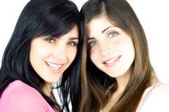 Счастливые подруги усмехаясь смотрящ камеру Стоковое Изображение