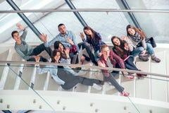 Счастливые предназначенные для подростков девушки и мальчики на лестницах школе или коллеже Стоковые Фото