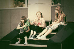 Счастливые предназначенные для подростков девушки сидя на шагах Стоковые Фотографии RF