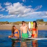 Счастливые предназначенные для подростков серферы говоря на береге пляжа Стоковое фото RF