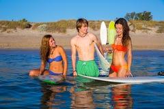 Счастливые предназначенные для подростков серферы говоря на береге пляжа Стоковая Фотография RF