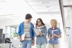Счастливые предприниматели обсуждая пока идущ в творческом офисе Стоковая Фотография RF
