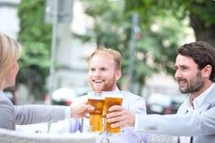 Счастливые предприниматели провозглашать стекла пива на внешнем ресторане Стоковое фото RF