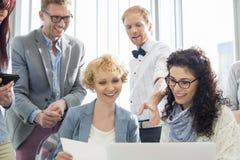 Счастливые предприниматели работая на компьтер-книжке в творческом офисе Стоковая Фотография