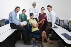 Счастливые работники центра телефонного обслуживания усмехаясь совместно стоковое фото rf