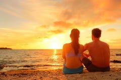 Счастливые романтичные пары наслаждаясь заходом солнца на пляже Стоковое Изображение