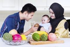 Счастливые родители дают плодоовощ к их ребенку стоковое фото rf