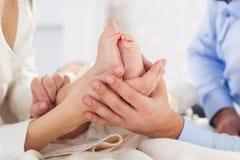 Счастливые родители держат childs foots руками Стоковое Изображение RF