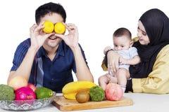 Счастливые родители и младенец с свежими фруктами стоковая фотография