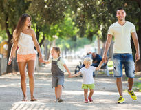 Счастливые родители с маленькими детьми в парке Стоковые Изображения RF