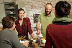 Счастливые друзья в кухне Стоковое фото RF