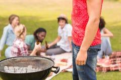 Счастливые друзья в парке имея барбекю Стоковые Фото
