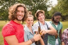 Счастливые друзья в парке имея барбекю Стоковые Изображения RF