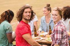 Счастливые друзья в парке имея обед Стоковое Фото