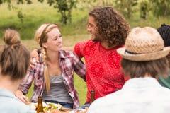 Счастливые друзья в парке имея обед Стоковые Фото