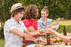 Счастливые друзья в парке имея обед Стоковые Изображения
