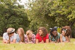 Счастливые друзья в парке имея пикник Стоковое фото RF